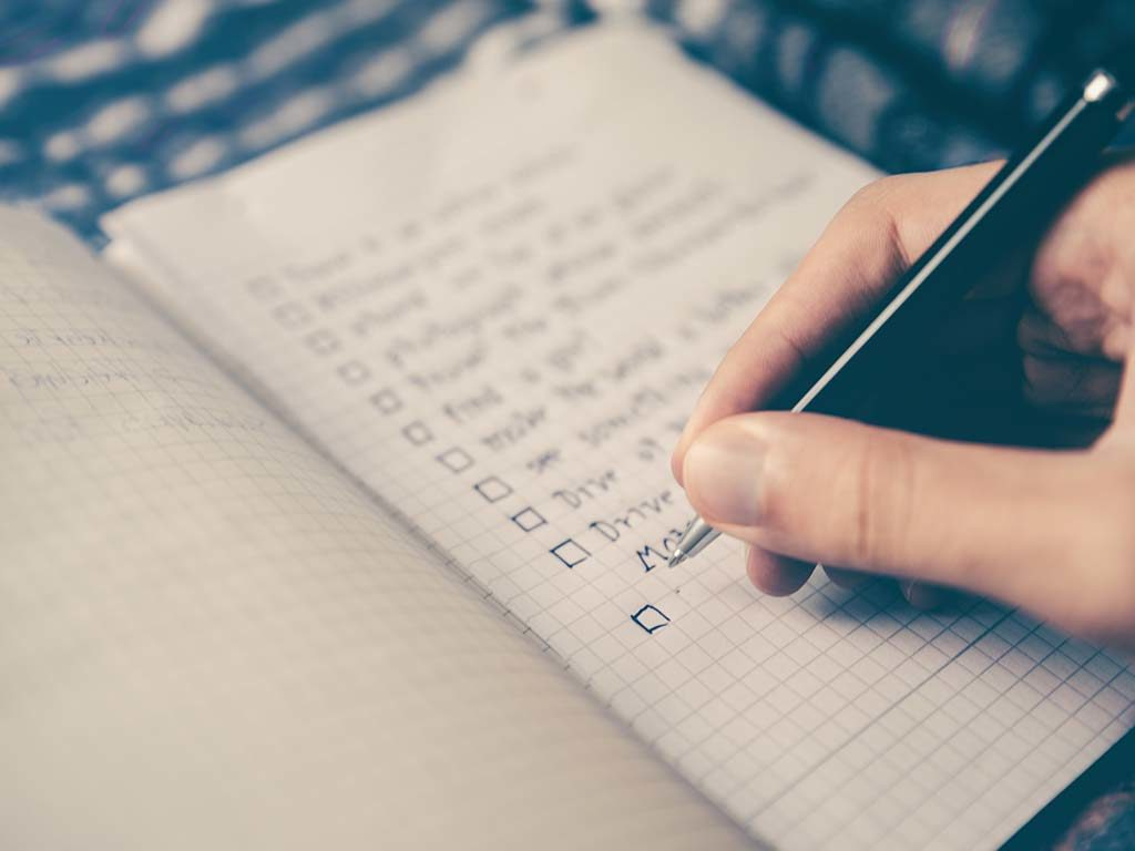Pen writing on checklist